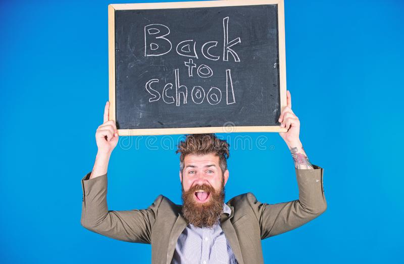 Teacher with tousled hair cheerful about school year beginning. Teacher bearded man holds blackboard with inscription. Back to school blue background. Keep stock images