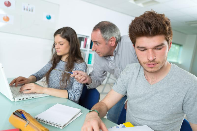 Teacher or tutor with students in classroom with laptop computer. Students stock photo