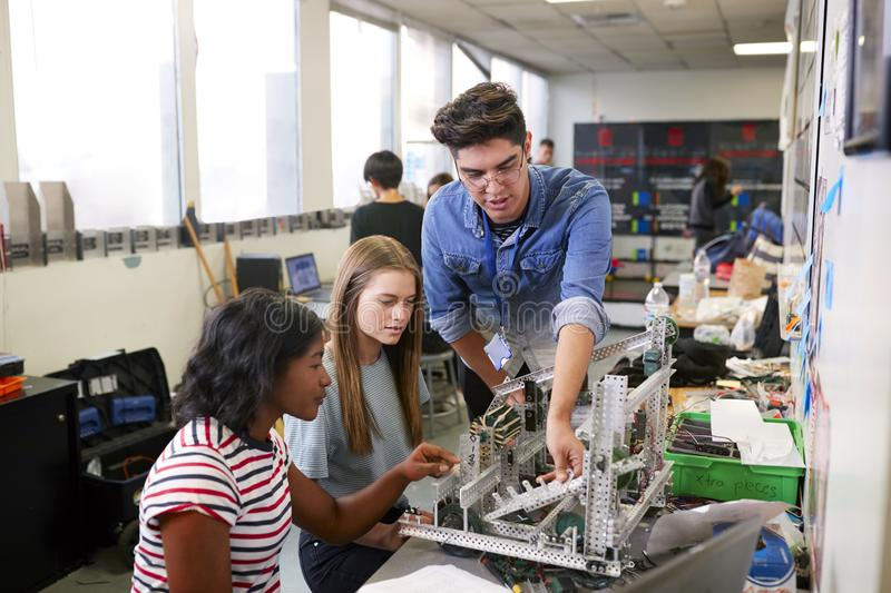 Teacher With Two Female College Students Building Machine In Science Robotics Or Engineering Class royalty free stock photo