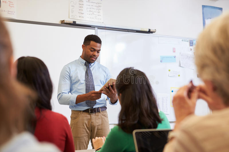 Teacher using tablet computer at an adult education class stock images