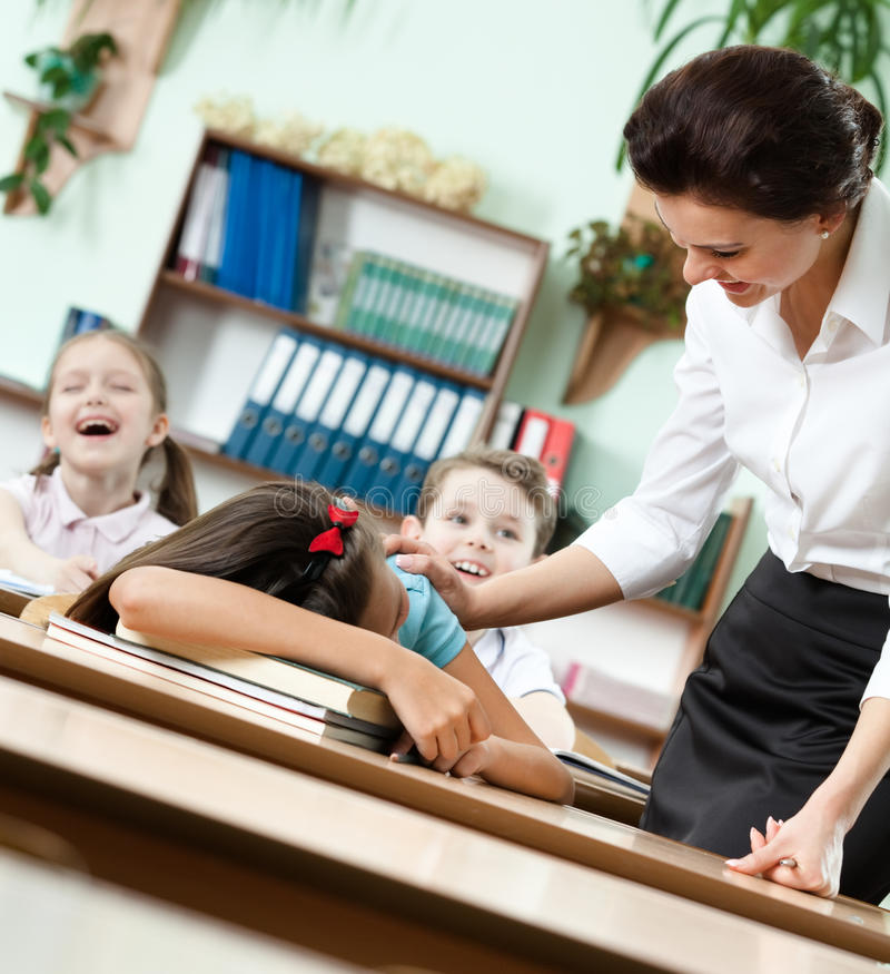 Download Teacher Wakes A Sleeping At The Desk Pupil Up Stock Photo - Image: 26219278