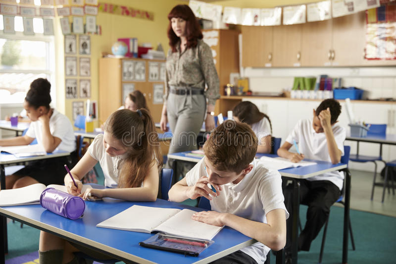 Teacher walking in her busy primary school classroom royalty free stock photo