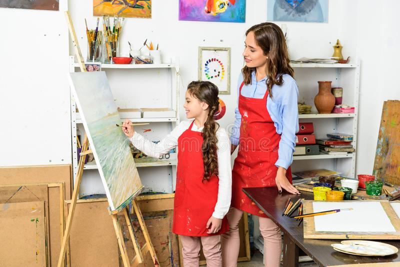 Teacher watching how pupil painting on canvas in workshop of. Art school royalty free stock images