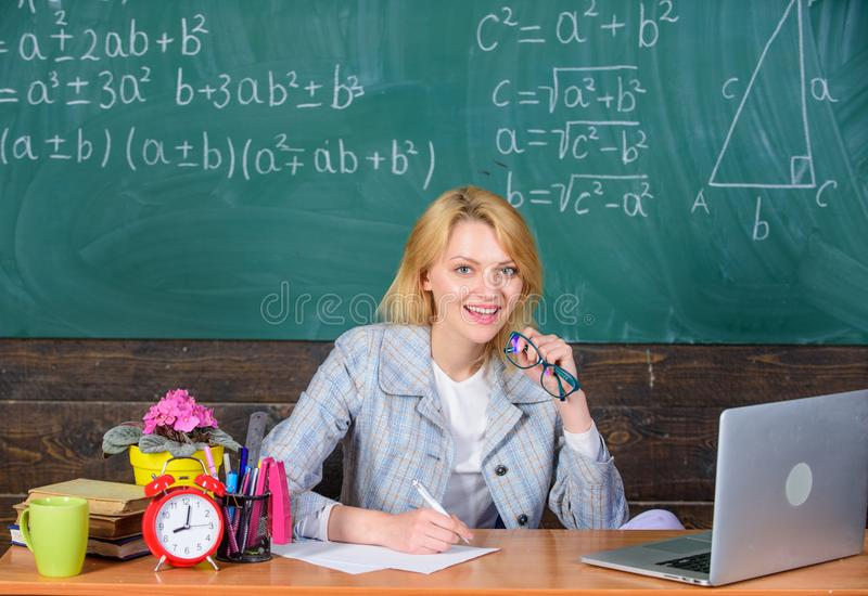 Teacher woman sit table chalkboard background. Excellent communicability and interpersonal skills. Organize class and. Make learning easy and meaningful process royalty free stock image