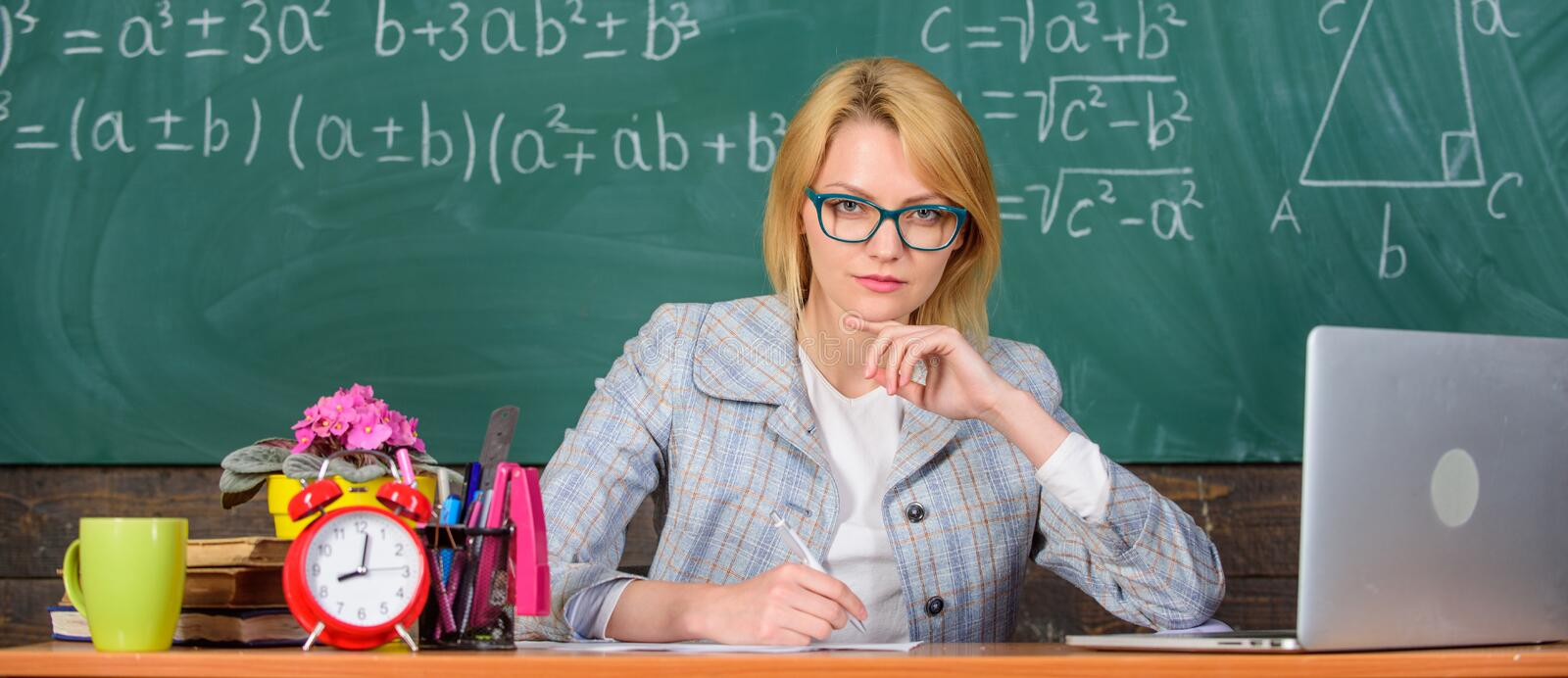 Teacher woman sit table classroom chalkboard background. Present lesson in comprehensive manner to facilitate learning. Create and distribute educational royalty free stock photos