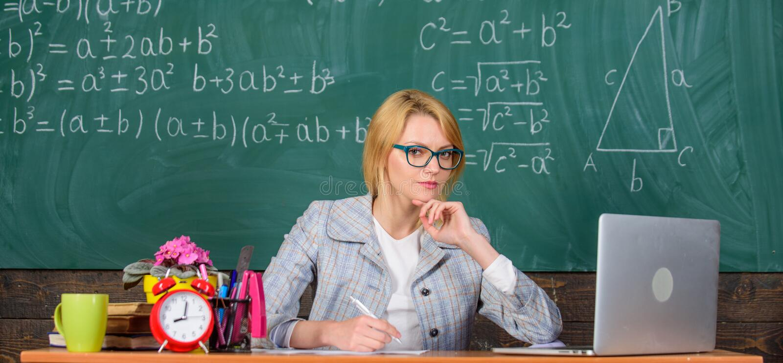 Teacher woman sit table classroom chalkboard background. Present lesson in comprehensive manner to facilitate learning. Promoting interactive learning. Create stock photos