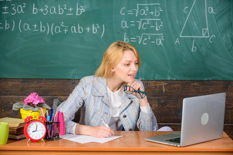Teacher woman sit table work laptop surfing internet chalkboard background. Present lesson in comprehensive manner use. Visual to facilitate learning. Organize royalty free stock photo