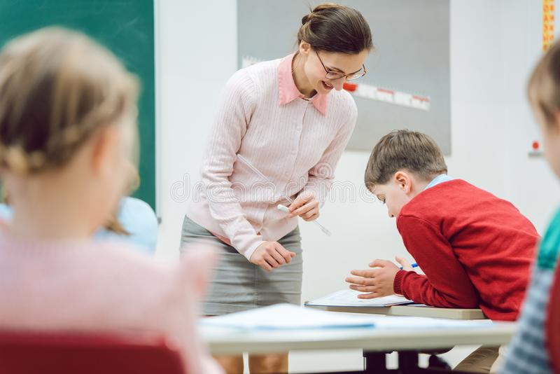 Teacher woman talking to student in class room. Teacher women talking to student in class room handing out test results royalty free stock image