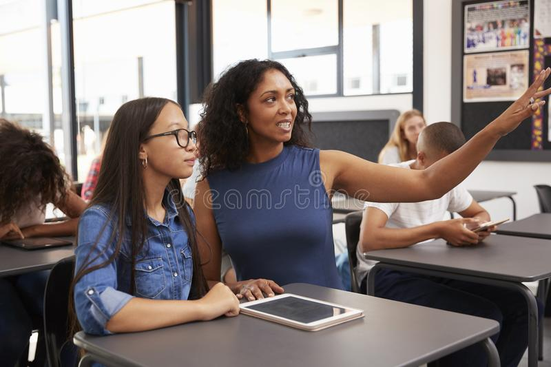Teacher working with teenage schoolgirl points to the board stock photography