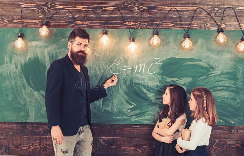 Teacher write with chalk on chalkboard. Little girls listen to bearded man at school board. Tutor teach children stock images