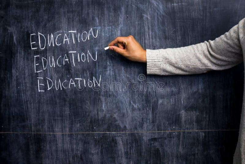 Teacher writing on blackboard. Education stock image