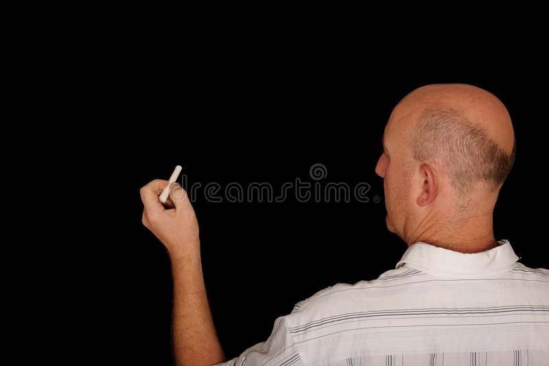 Teacher writing on Chalkboard stock photo