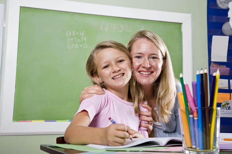 Teacher and young student in class writing royalty free stock photos
