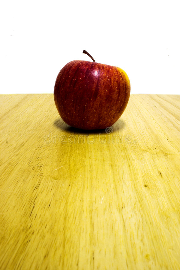 Teachers apple. Red apple sitting on the edge of a wooden desk royalty free stock image