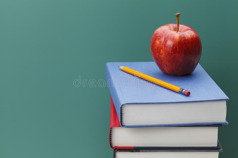 Teachers Chalk Board. Close up of Classroom Chalk Board, Books and Apple with Copy Space stock photos