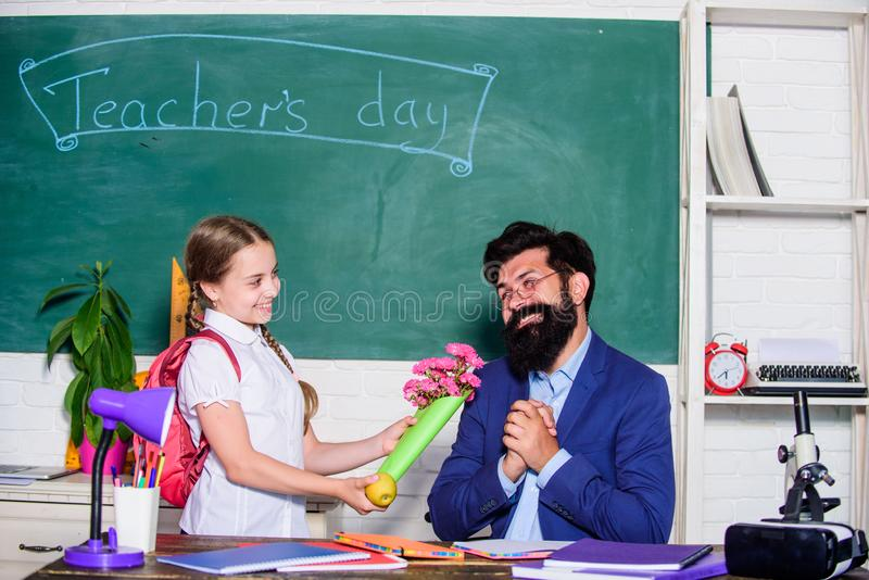 Teachers day. Daugghter and father with flowers. small school girl kid with flower bouquet. knowledge day is 1 september. Back to school. Happy teachers day stock photo