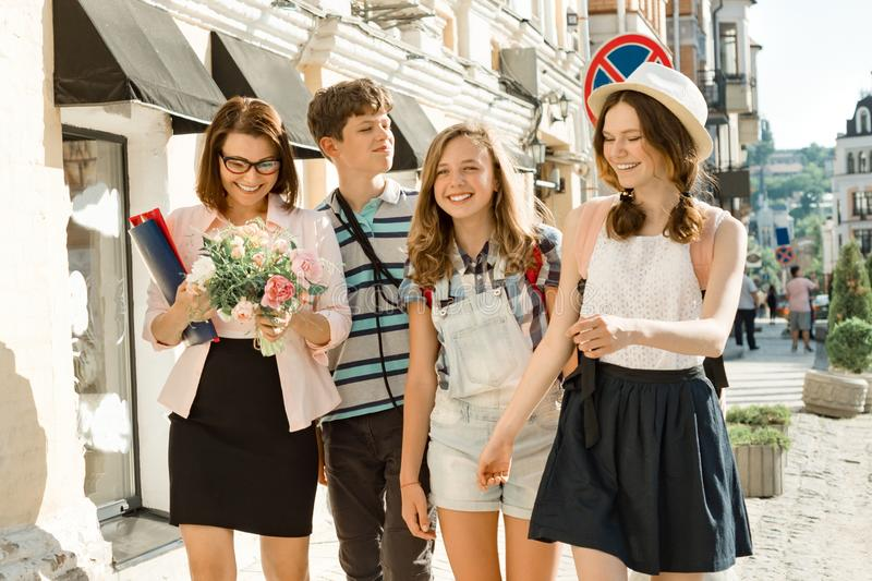 Teachers Day, outdoor portrait of happy middle aged female high school teacher with bouquet of flowers and group students royalty free stock image