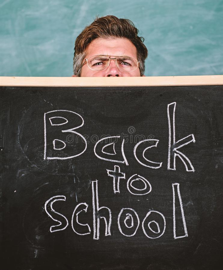 Teachers life full of stress. Teacher or school principal welcomes inscription back to school. Educator hiding behind. Blackboard. Teacher peeking out of stock photography