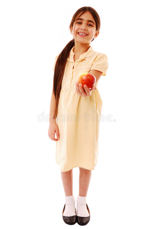Teachers pet. Well behaved pupil holding out apple isolated on white stock photo