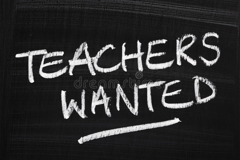 Teachers Wanted. Written in white chalk on a just wiped blackboard royalty free stock photos