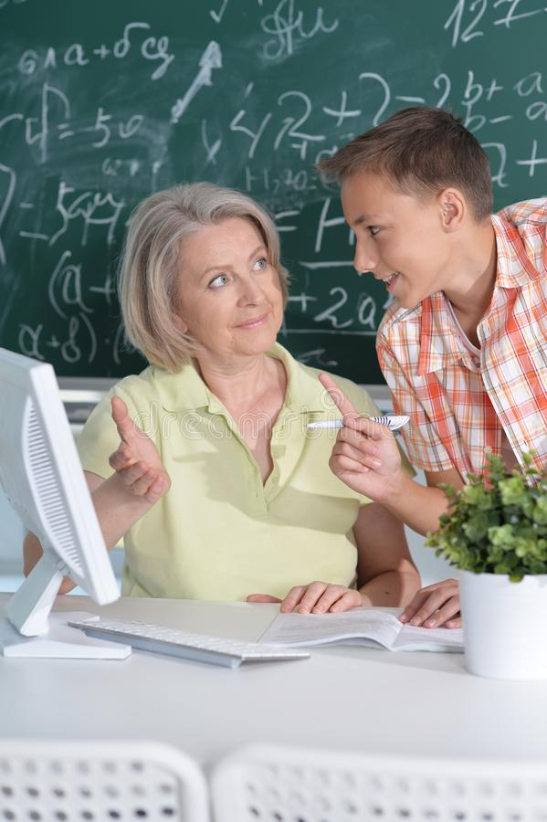 Teachers working with pupil. In computer class stock photos