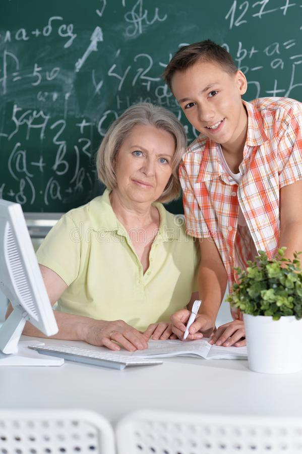 Teachers working with pupil. In computer class stock images