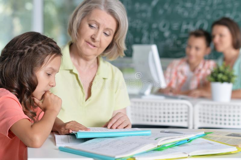 Teachers working with pupils. In computer class royalty free stock image