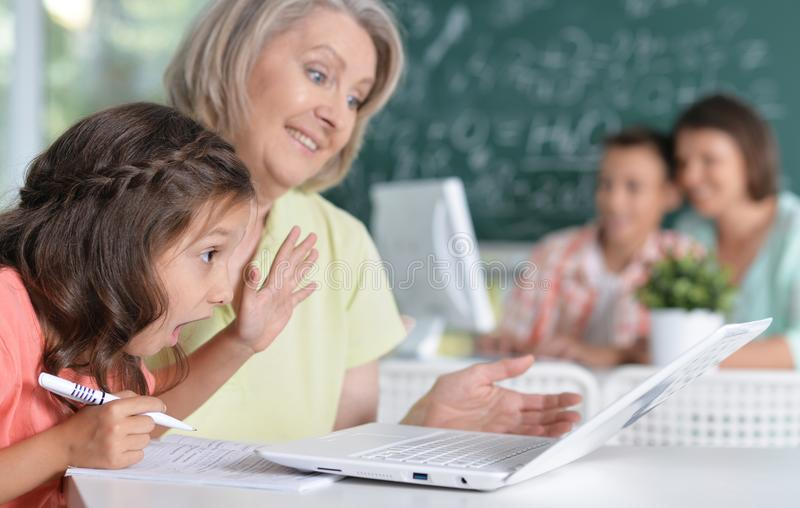 Teachers working with pupils. In computer class stock photo
