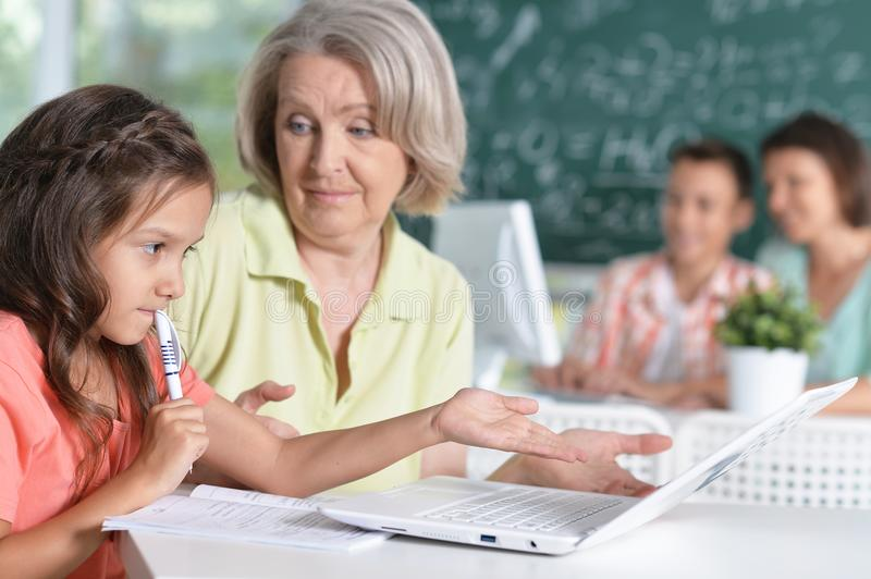 Teachers working with pupils. In computer class stock photography