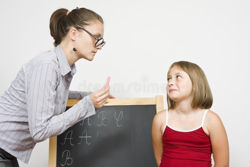 Teaching. A dour female teacher explaining the lesson to a little girl royalty free stock photo