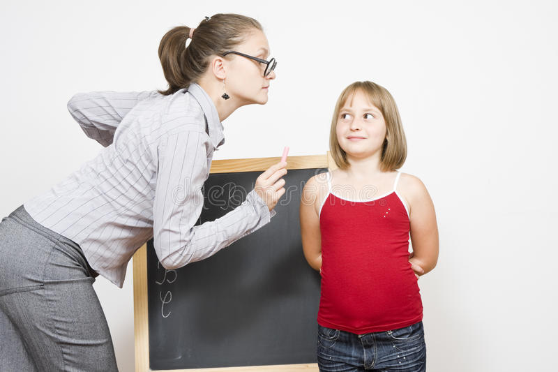 Teaching. A dour female teacher explaining the lesson to a little girl stock photo