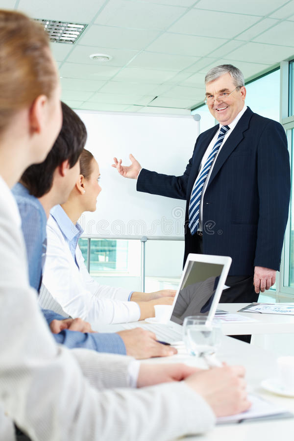 Teaching. Senior business men showing something on a whiteboard to his colleagues stock image