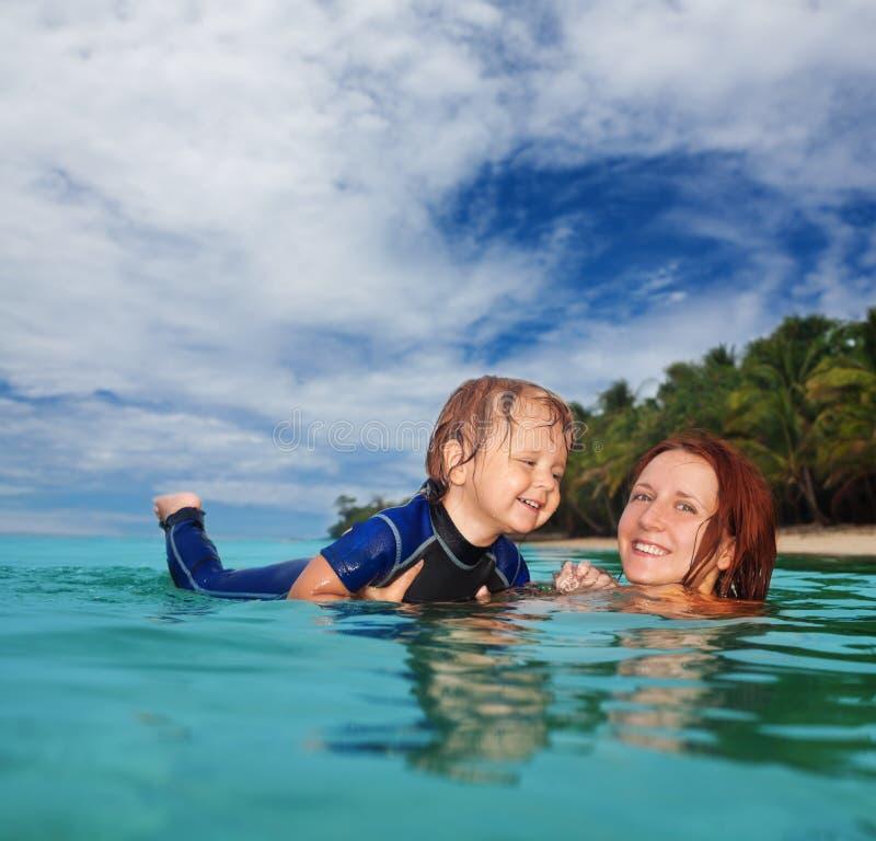 Teaching baby to swim stock images