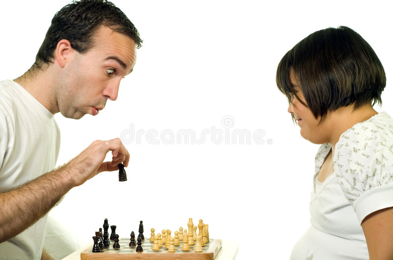 Teaching Chess. A young man teaching his daughter how to play chess stock images
