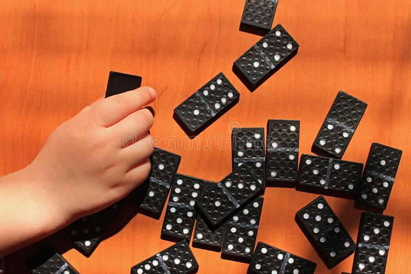 Teaching children to play dominoes game on a wooden background. Teaching children to play dominoes. Children`s hand holds domino tile on a wooden table. A set of royalty free stock images