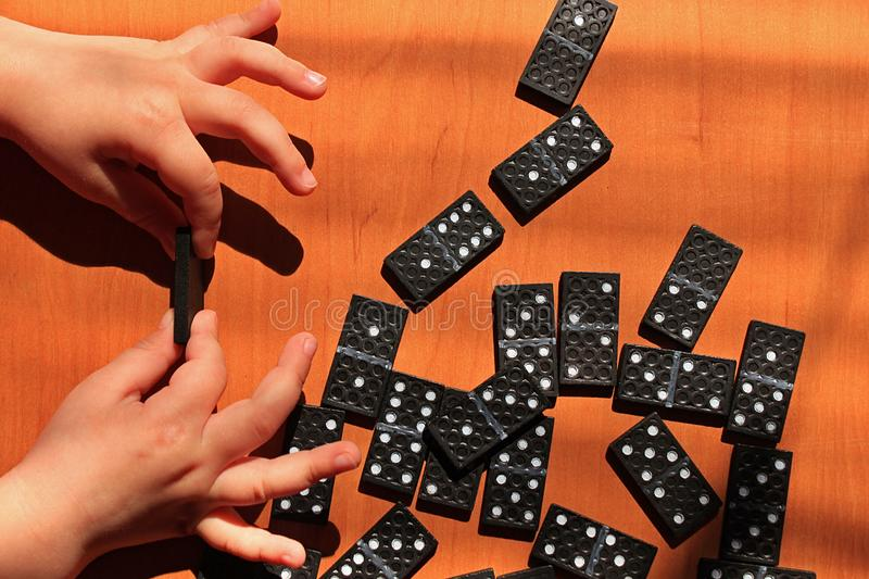 Teaching children to play dominoes game on a wooden background. Teaching children to play dominoes. Children`s hand holds domino tile on a wooden table. A set of stock photography