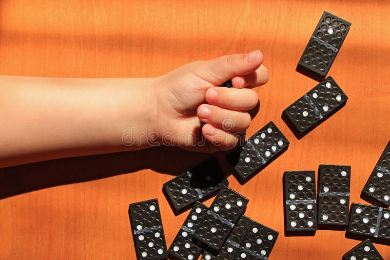 Teaching children to play dominoes game on a wooden background. Teaching children to play dominoes. Children`s hand holds domino tile on a wooden table. A set of royalty free stock photo