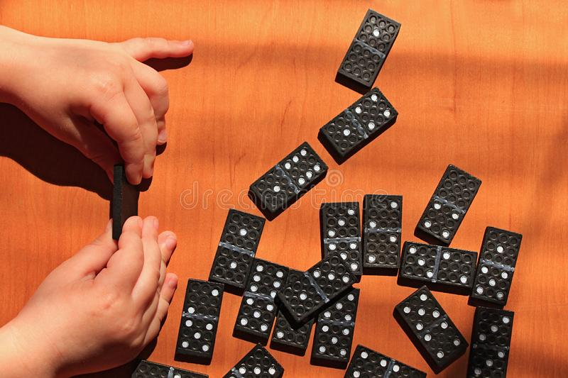 Teaching children to play dominoes game on a wooden background. Teaching children to play dominoes. Children`s hand holds domino tile on a wooden table. A set of stock images