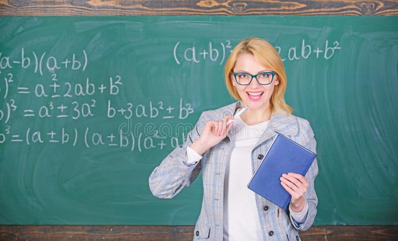 Teaching complex multifaceted activity. Teacher smart woman with book explain topic near chalkboard. What makes great stock photos