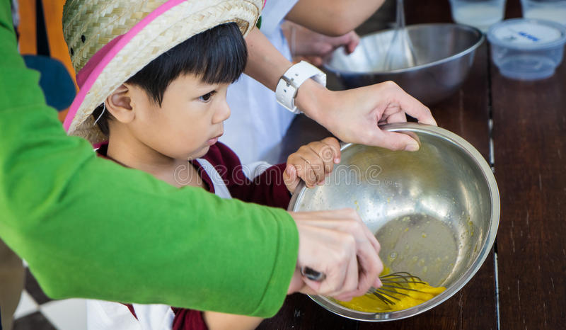 Teaching Japanese baby boy in a cooking class stock images
