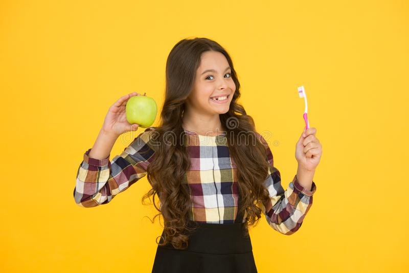 Teaching kids cleaning teeth. Oral hygiene. Girl cute hold toothbrush and apple. Child girl hold brush tooth with paste. Child girl happy face care hygiene stock photography