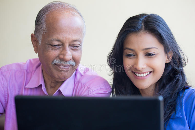 Teaching at the laptop. Closeup portrait, sitting young women showing elderly men to use black laptop, happy at what they see , indoors background royalty free stock photography