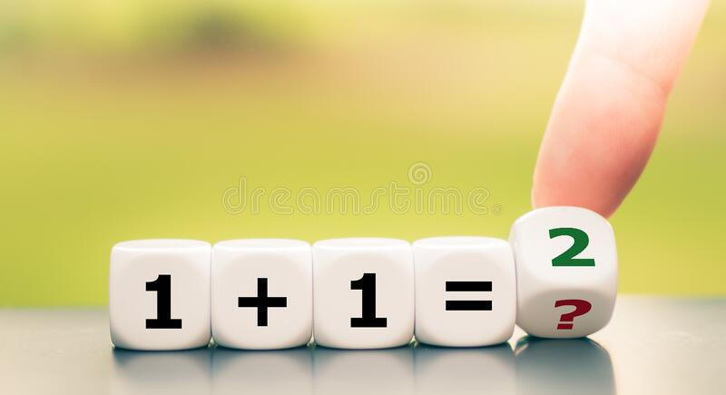 Teaching mathematics. Hand turns a dice and solves and equation.  royalty free stock images