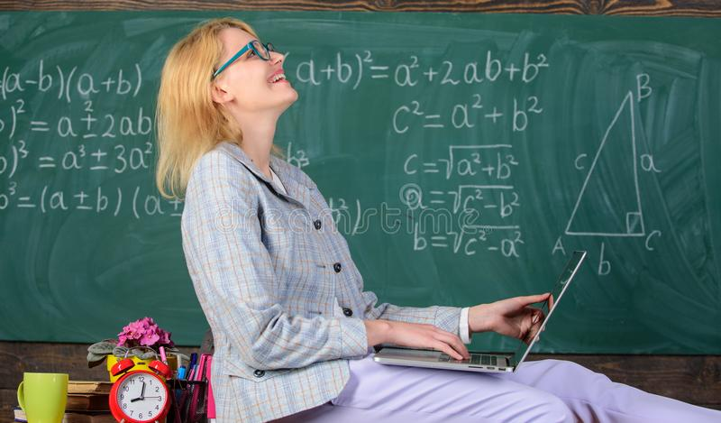 Teaching in non formal atmosphere. Woman teacher hold laptop sit table classroom chalkboard background. Teacher of stock photo