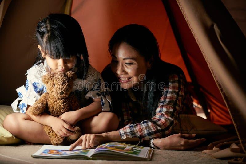 Teaching reading. Smiling Vietnamese women teaching her little daughter reading stock image