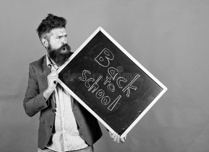Teaching stressful occupation. Take it easy. Teacher with tousled hair stressful about school year beginning. Teacher. Bearded man holds blackboard with stock photography