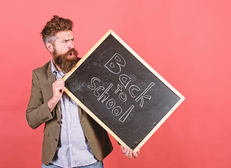 Teaching stressful occupation. Take it easy. Teacher with tousled hair stressful about school year beginning. Teacher. Bearded man holds blackboard with royalty free stock photo