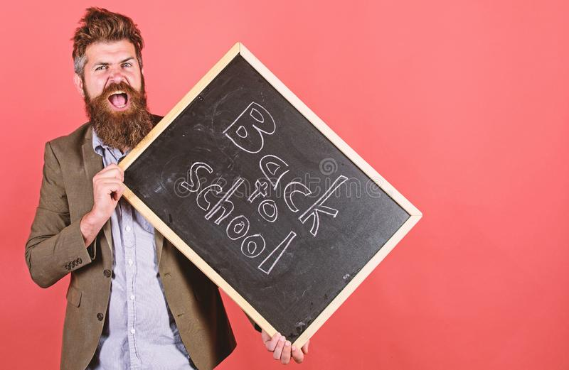 Teaching stressful occupation. Teacher with tousled hair stressful about school year beginning. Stay positive. Teacher. Bearded man holds blackboard with stock image