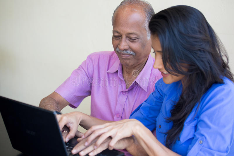 Teaching typing. Closeup portrait, sitting young women showing elderly men to use black laptop, happy at what they see , indoors background stock photography