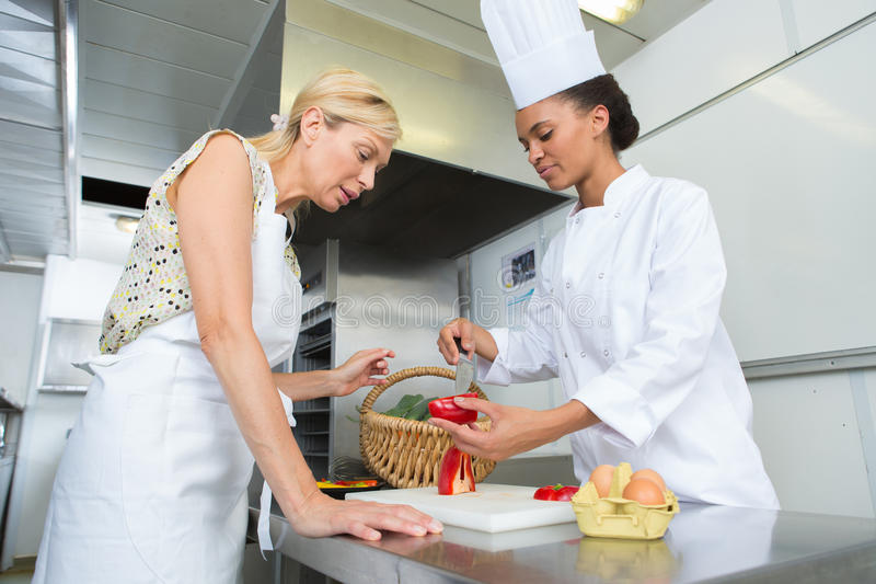 Teaching young chef`s assistant stock photos